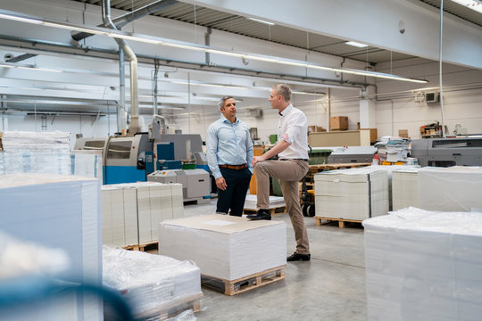 Two colleagues talking in a factory
