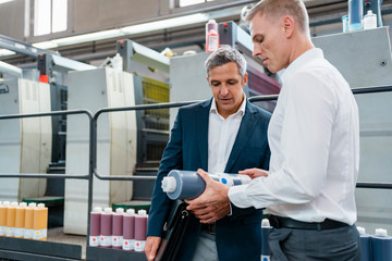 Two businessmen examining product in a factory