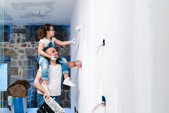 Girl sitting on father's shoulders painting the wall of her new house