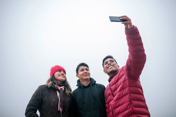 Young Mexican friends taking a selfie on a foggy day Wall mural