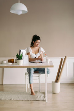 Young woman sitting at table at home