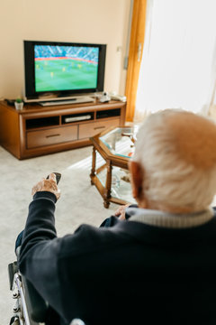Back view of senior man watching TV at home using remote control