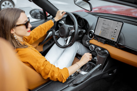 Young and cheerful woman driving sports car with a digital touchscreen with launched controlling program on the front dashboard