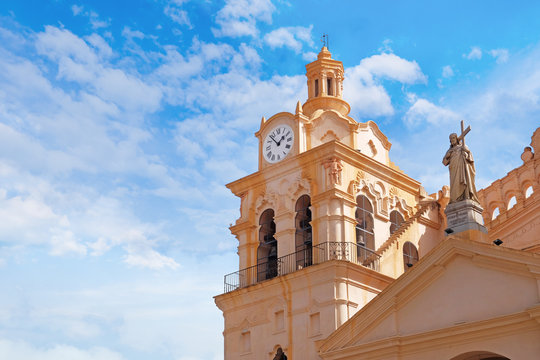 Detailed view of Cathedral of Cordoba, Argentina, against a blue sky covered by white clouds.
