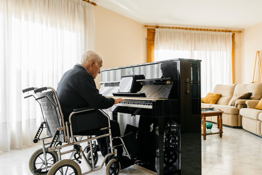 Senior man sitting in wheelchair playing piano at home