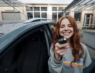 Portrait of happy redheaded woman beside car holding key
