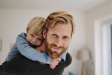 Portrait of smiling father carrying son piggyback at home
