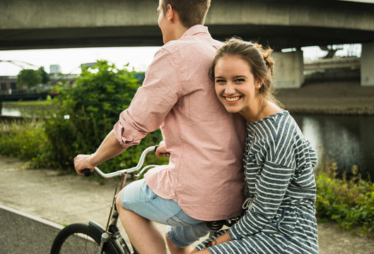 Young couple driving together on bicycle