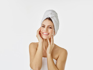 Portrait of smiling woman with hairs wrapped in towel against white background