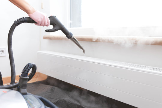 Employee cleaning service processes steam heating radiator