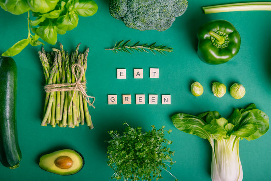 Top view set of healthy raw vegetables on the green background with Eat Green message on wooden blocks. Vegetarian and vegan diet. Veganism concept. Sustainable lifestyle, good, real plant-based foods