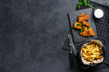 Fish and chips, traditional English food. Black background. Top view. Copy space