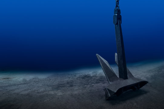 Ship anchor underwater on bottom in clean ocean water at anchorage. Marine shipping concept.