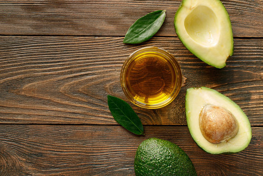 Avocado oil for healthy skin and hair on a wooden background.