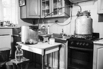 Old-fashioned moonshine machine for creating homemade strong alcohol in the kitchen. Process of distillation, general view. Story about an aged way of distilling moonshine at home. Monochrome effect