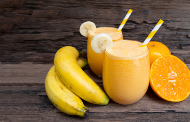 Poster Juice Banana and orange smoothies yellow colorful fruit juice milkshake blend beverage healthy high protein the taste yummy In glass,drink to lose weight drink episode on wooden background.