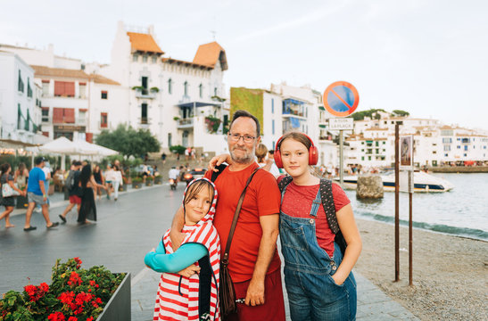 Outdoor portrait of happy father with young kids, family spending time together by the sea