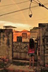 criança observa arco iris do portão em um bairro do rio de janeiro