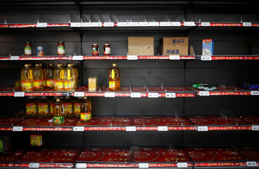 An empty shelf is pictured as people stock up on food supplies, a day after Singapore raised the coronavirus outbreak alert level to orange, at a supermarket in Singapore