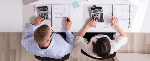 Two Businesspeople Calculating Invoice