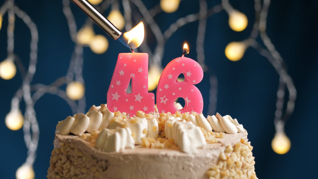 Birthday cake with 46 number candle on blue backgraund set on fire by lighter. Close-up view