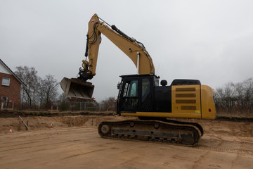 a building site there is a yellow excavator preparing the ground for foundations