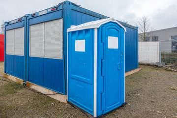 a construction site a blue construction site toilet stands next to a blue container