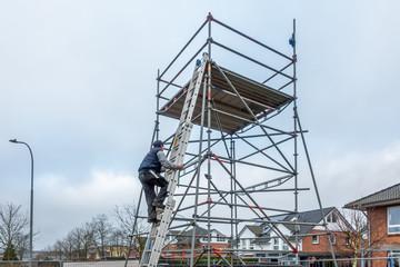 man climbs onto scaffolding on an extension ladder