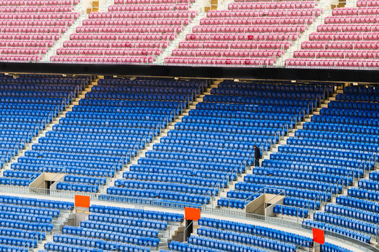 Empty stands of a stadium with empty seats of blue and red, and a maintenance person