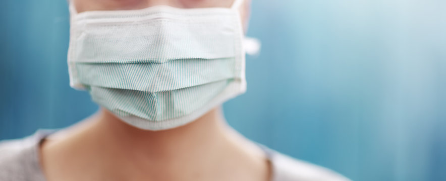 young woman in medical face protection mask indoors on blue background
