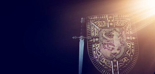 photo of shield knight armor and sword over dark background. Medieval period concept