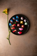Overhead view of Collection of  Chocolate candy on tray and yellow flower