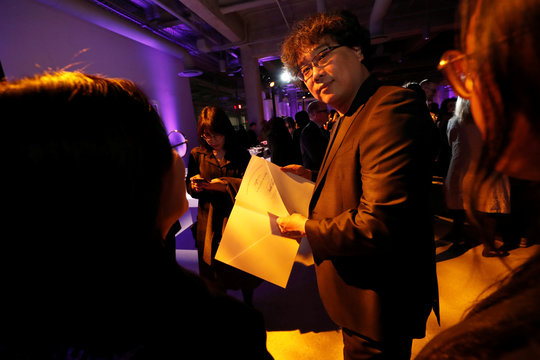 Director Joon Ho holds his certificate of nomination at the Academy's party for the Best International Feature Film nominees at the Academy Museum of Motion Pictures in Los Angeles