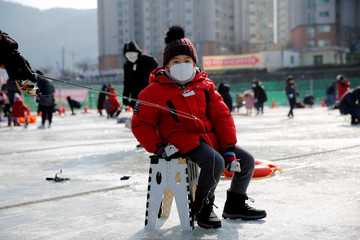 Boy wearing a mask to prevent contacting a new coronavirus fishes for trout on a frozen river during the Ice Festival in Hwacheon