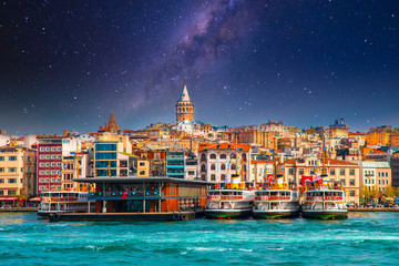 Galata Tower in istanbul City of Turkey. View of the Istanbul City of Turkey with bosphorus, seagulls and boats at bright sky and sunset or night.  Fotomurales