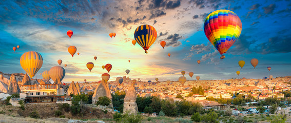 Poster de jardin Montgolfière / Dirigeable Colorful hot air balloons flying over at fairy chimneys in Nevsehir, Goreme, Cappadocia Turkey. Hot air balloon flight at spectacular Cappadocia Turkey.