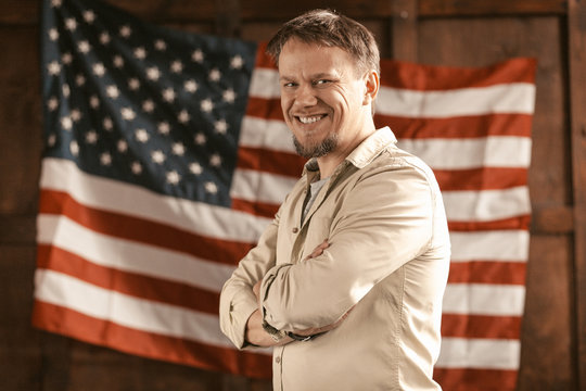 Citizen Of America Smilles Confident Standing On American Flag Background