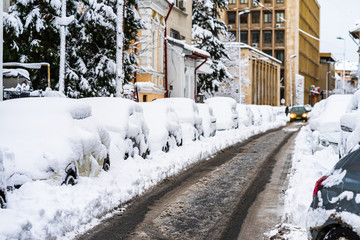 Cars covered with snow from the first snow fall of the year. Winter concept, snowy cars parked on the street, deep layer of snow