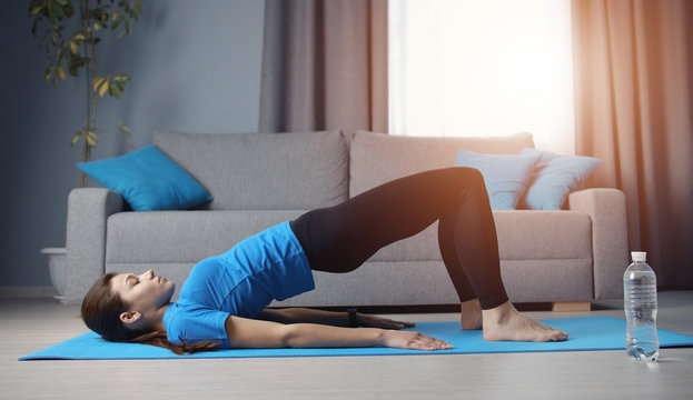 Young lady doing bridge pose training on yoga mat on floor in apartment