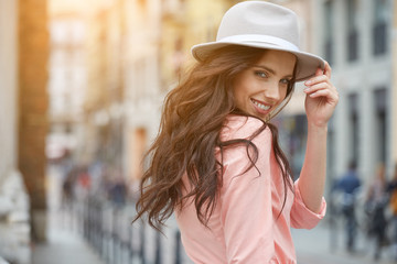 Close-up Fashion woman portrait of young pretty trendy girl posing at the city in Europe,summer street fashion,holding retro fedora hat popular until the 60s.