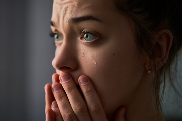 Sad desperate crying female with folded hands and tears eyes during trouble, life difficulties, loss and emotional problems