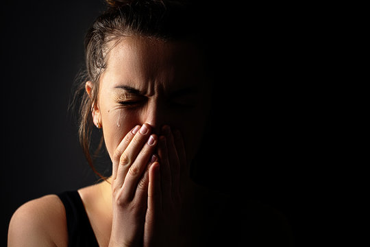 Sad grieving crying female with folded hands and tears eyes on a dark black background during trouble, life difficulties, loss and emotional problems. Copy space