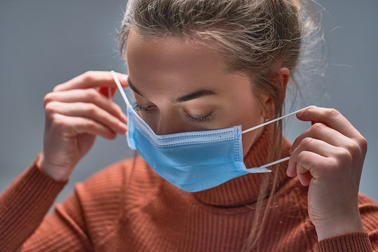Healthy woman putting on medical protective mask to health protection and prevention during flu virus outbreak, epidemic and infectious diseases