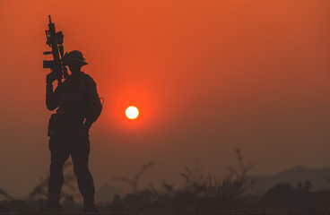 In de dag Baksteen silhouette of Soldier backdrop of sunset sky.Soldier with machine gun patrolling