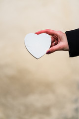 Woman hand holding a wooden heart with copy space. Valentine's day concept, a symbol of love