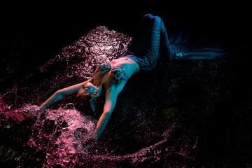 Mermaid splashing in water under pink light