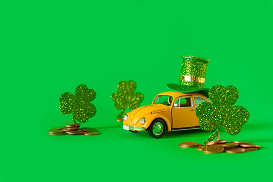 Minsk, Belarus - February 2020: holiday of St. Patrick's Day A yellow toy car is carrying a hat and clover holiday symbol on a green background. Holiday Irish Patrick's Day postcard with retro car