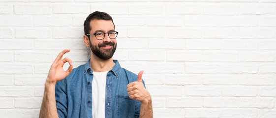 Handsome man with beard over white brick wall showing ok sign and thumb up gesture