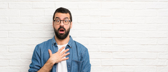 Handsome man with beard over white brick wall surprised and shocked while looking right