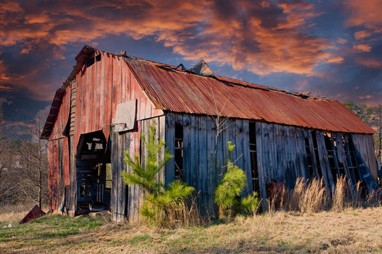 An old barn with a rusty roof in a rural area